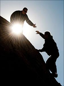 man helpt andere man om een berg te beklimmen